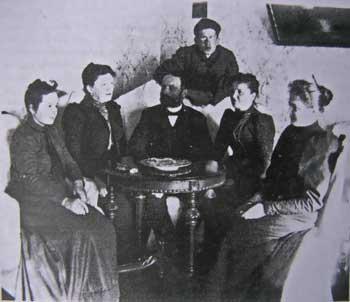 В гостинной дома в Ольховце сидят (слева направо): Е.Д. (Геня) Воейкова, Н.А. Худекова, Д.А. Воейков, А.А. Воейкова, А.Д. (Лина) Воейкова. Конец 1890-х гг.